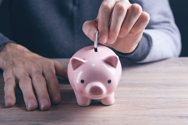 Mão colocando moeda no cofrinho