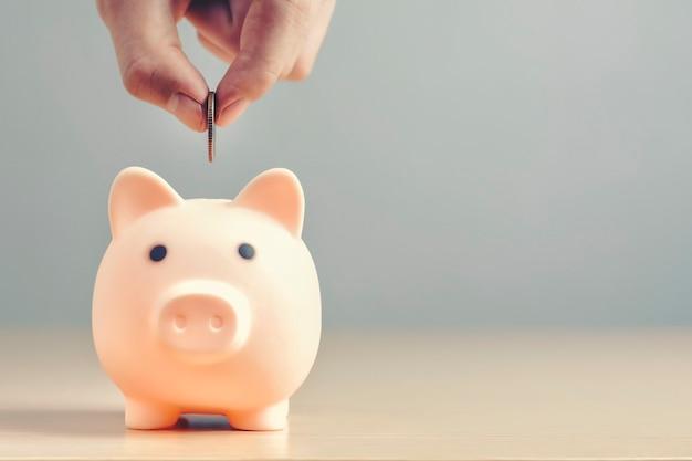 Mão colocando moedas com um cofrinho ou caixa de dinheiro em um piso de madeira para economizar dinheiro para investimento.
