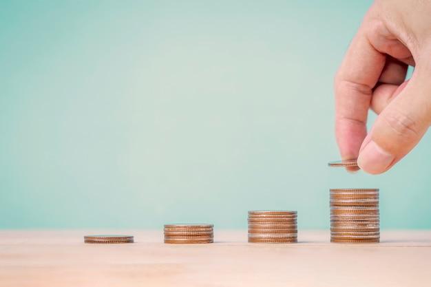 Mão colocando moedas em pilhas de moedas na mesa de madeira e fundo de hortelã