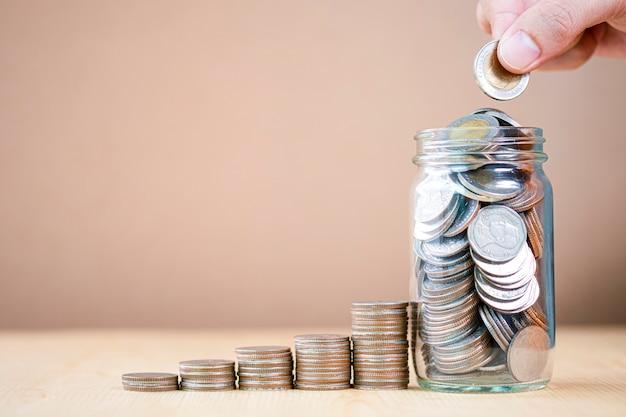 Mão colocando moedas em uma jarra
