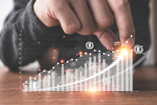 Mão colocando moedas empilhamento com gráfico virtual e aumentar a seta na frente do empresário. investimento empresarial e salvando o conceito de lucro.