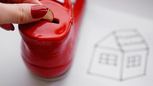 Mão colocando moedas na caixa do dinheiro. desenhando uma casa em um lençol branco próximo a uma caixa