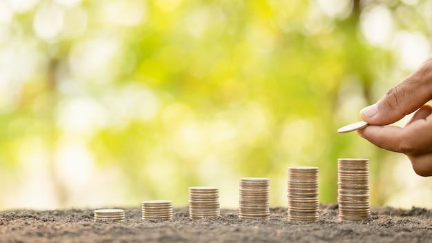 Mão colocando moedas na pilha na prancha de madeira com verde desfocar o fundo