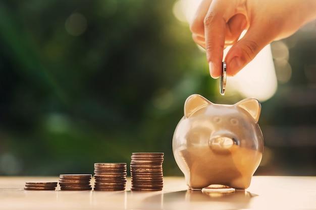 Mão colocando moedas no cofrinho com pilha de dinheiro na mesa