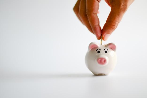 Mão colocando moedas no cofrinho. economizando dinheiro, plano futuro, abra um depósito bancário e um conceito financeiro.
