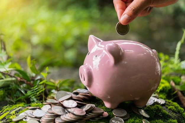 Mão colocando moedas no cofrinho para economizar dinheiro. conceito de finanças e contabilidade