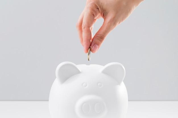 Mão colocando moedas no cofrinho