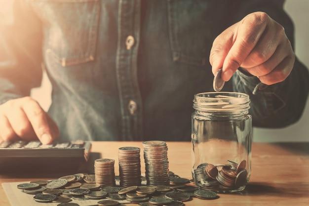 Mão colocando moedas no jarro de vidro para poupar dinheiro finanças e contabilidade conceito