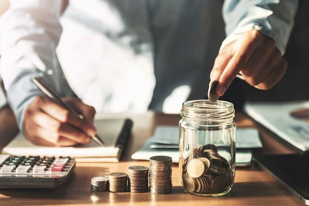 Mão colocando moedas no jarro