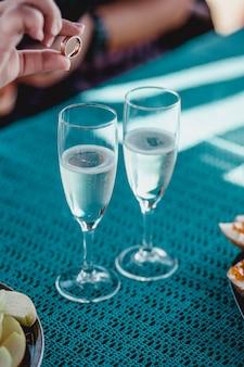 Mão colocando o anel na taça de casamento com espumante champanhe