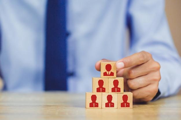 Mão, colocando o bloco de cubo de madeira na pirâmide superior, gestão de recursos humanos e conceito de negócio de recrutamento