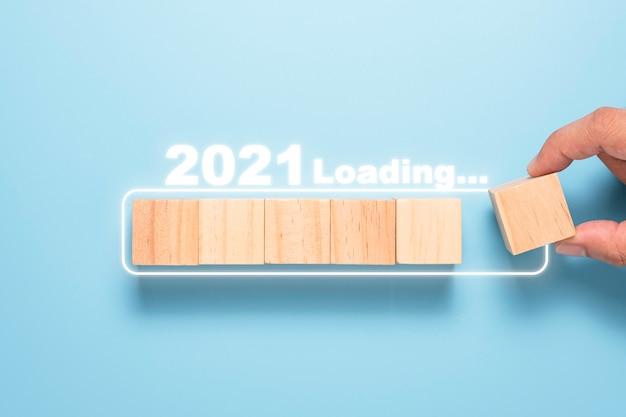 Mão colocando o bloco de cubos de madeira no bloco branco para contagem regressiva e carregamento até 2021. feliz ano novo para iniciar um novo projeto e conceito de negócio.
