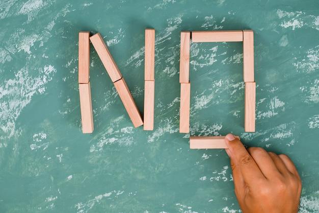 Mão colocando o bloco de madeira.