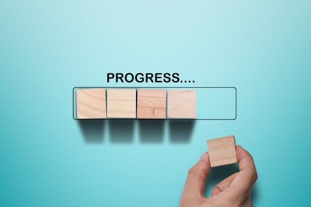 Mão, colocando o cubo de madeira no bloco de retângulo infográfico virtual com formulação de progresso. conceito progressivo de trabalho.
