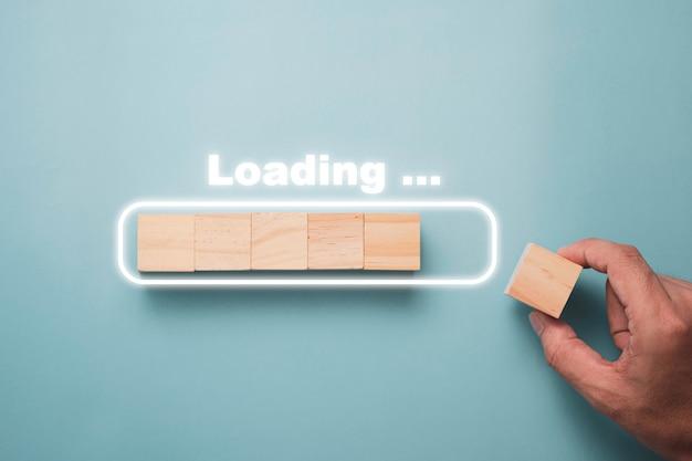 Mão, colocando o cubo de madeira no bloco de retângulo infográfico virtual com texto de carregamento. trabalho e conceito progressivo de download eletrônico.