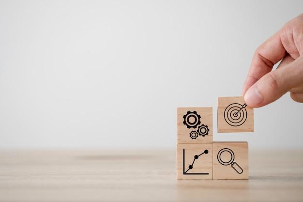Mão, colocando o dardo da tela de impressão e o cubo de madeira da placa alvo com gráfico de vidro da lupa e roda dentada. alvo de investimento e conceito de negócio.