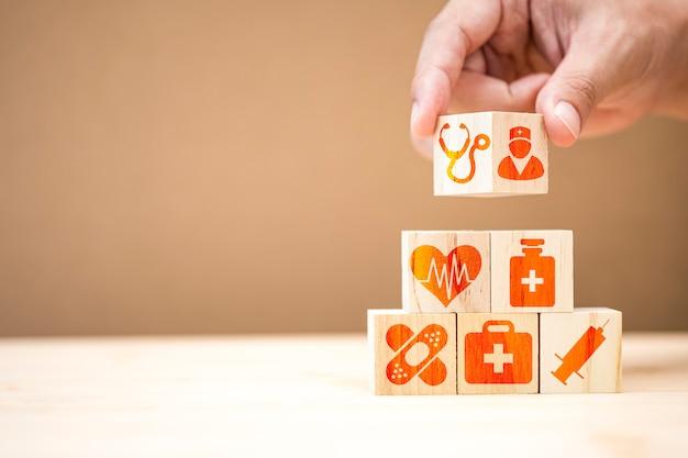 Mão, colocando o empilhamento de cubos de madeira do ícone de medicina e hospital de saúde na mesa.