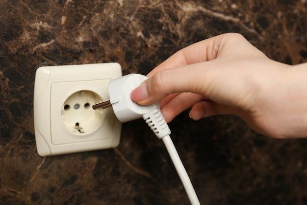 Mão colocando o plugue na tomada elétrica