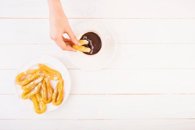 Mão, colocando o pretzel no molho de chocolate na mesa