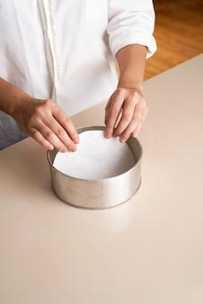 Mão colocando papel redondo na bandeja de bolo