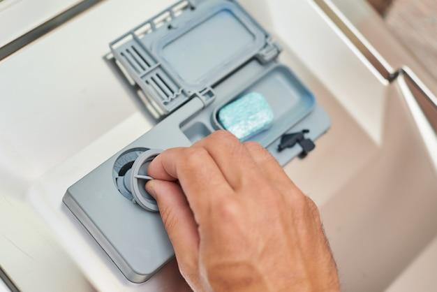 Mão colocando sabão tablet na máquina de lavar louça, close-up. conceito de aparelho doméstico de cozinha