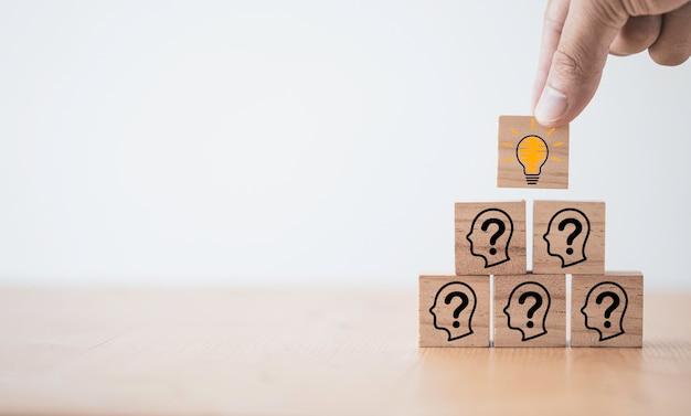 Mão colocando um bloco de cubo de madeira que imprime o ícone de lâmpada de tela no rosto com um ponto de interrogação