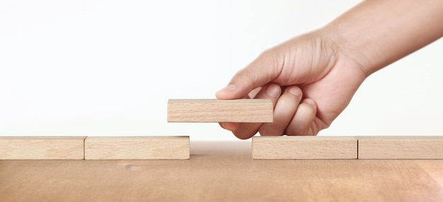 Mão colocando um bloco de madeira, planejamento de gerenciamento de projetos no negócio