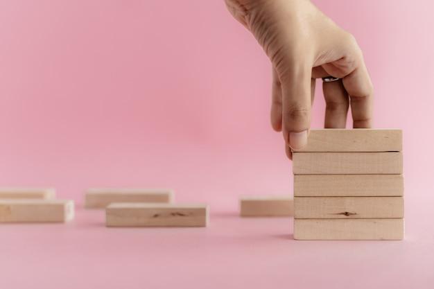 Mão, colocando um brinquedo de madeira no fundo rosa