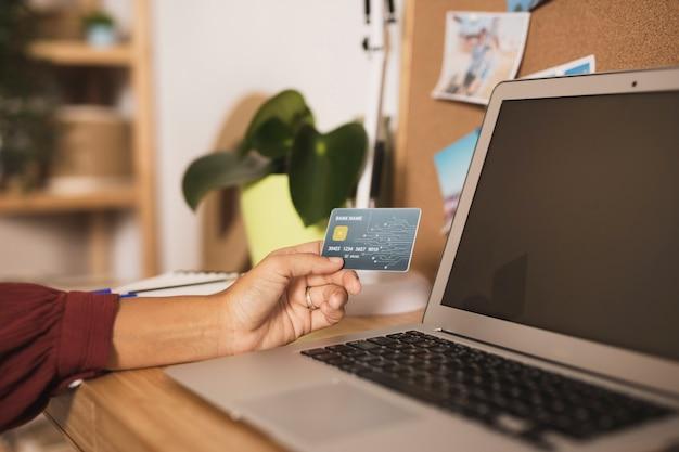 Mão, colocando um cartão ao lado de um laptop mock up