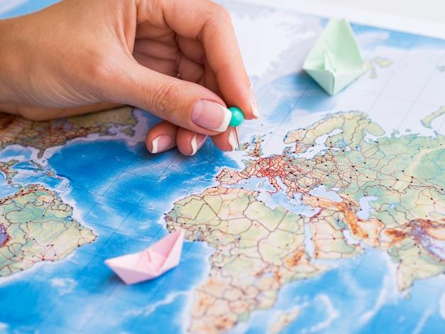 Mão colocando um pontinho no mapa