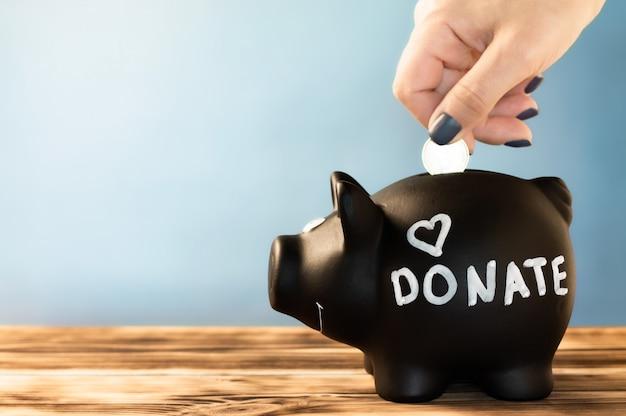 Mão colocando uma moeda em um cofrinho preto com uma etiqueta de doação de giz no azul
