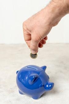 Mão colocando uma moeda em um cofrinho