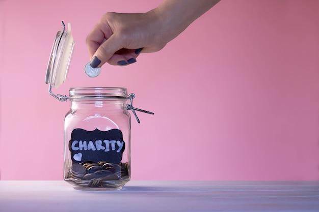 Mão colocando uma moeda em uma jarra de vidro com moedas com um giz