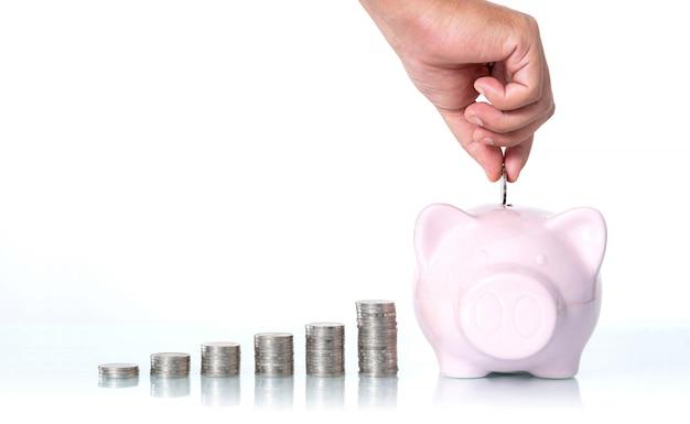 Mão, colocando uma moeda no cofrinho em branco