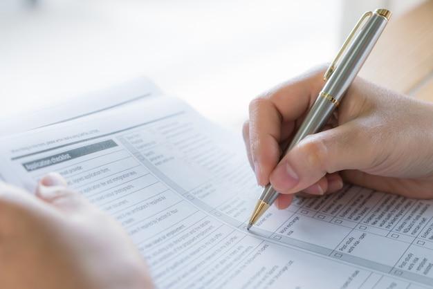 Mão com a pena sobre o formulário de candidatura