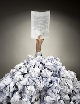 Mão com acordo estende-se de uma pilha de papéis