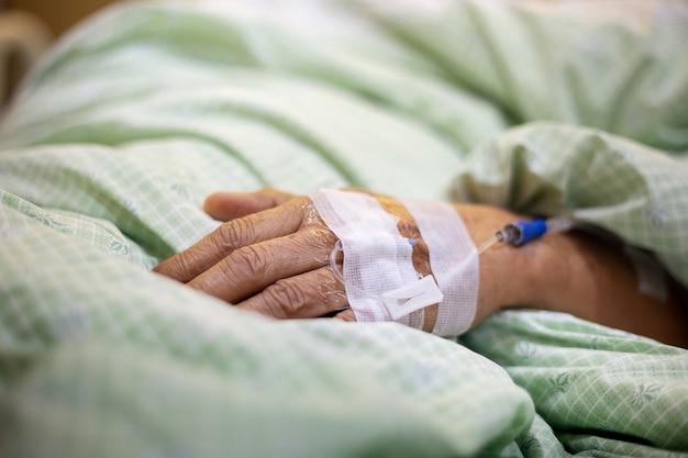 Mão com agulha para receber solução salina, médica e vitamina para curar paciente após a cirurgia.