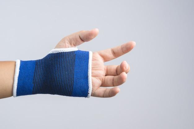 Mão com apoio de punho elástico e gesto ferido