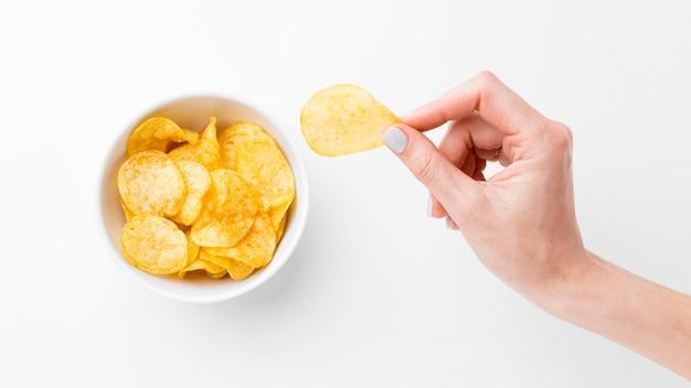 Mão com batatas fritas