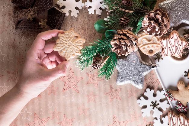 Mão com biscoito de natal, comendo biscoitos, decoração de natal, em um fundo de estrelas. ceia de natal, compartilhando com a familia