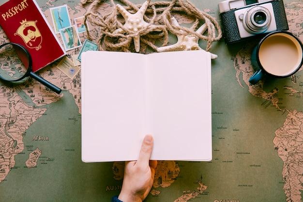 Mão com bloco de notas na mesa com itens turísticos