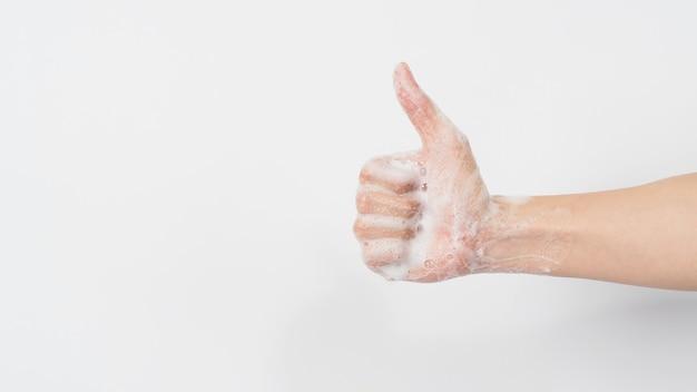 Mão com bolhas de sabão de espuma fazendo um sinal de gosto ou polegar para cima