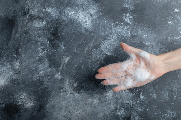 Mão com bolhas de sabão, mostrando a mão no mármore.