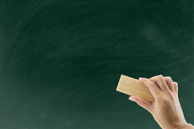 Mão com borracha apaga o quadro-negro, mão com lápis de limpeza de laranja