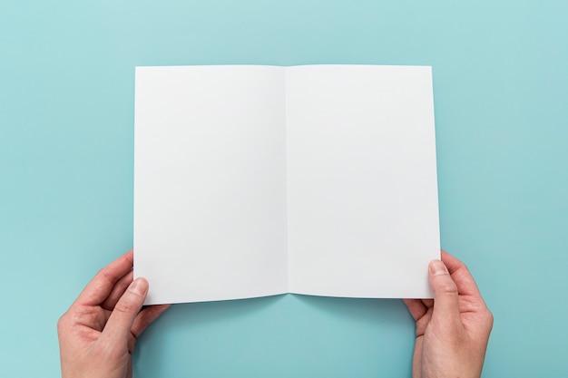 Mão com brochura dobrada