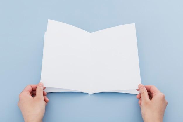 Mão com brochura em branco
