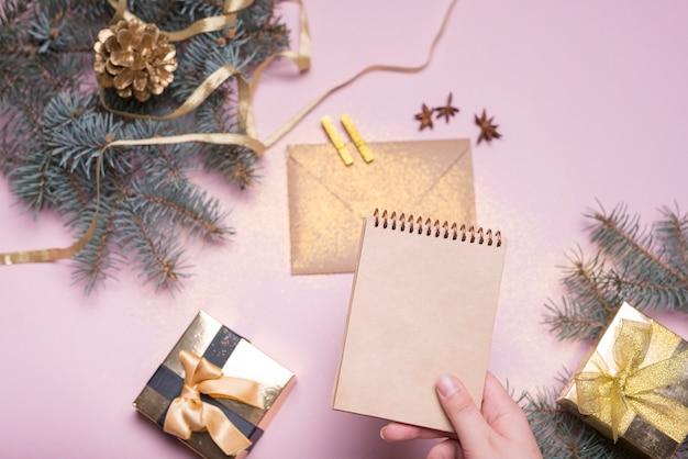 Mão com caderno perto de caixas de presentes, galhos de pinheiro, envelope e fita