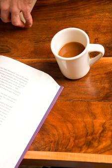 Mão com café e livro