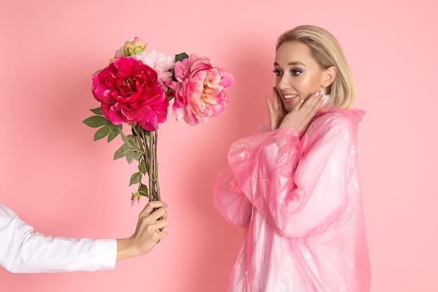 Mão com camisa branca dá buquê de peônias para jovem loira em fundo rosa no estúdio.