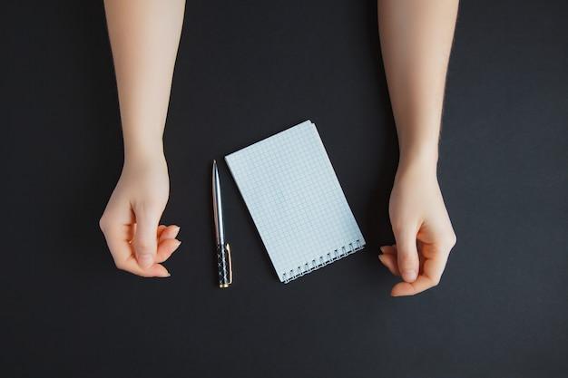 Mão com caneta e papel branco, na mesa escura